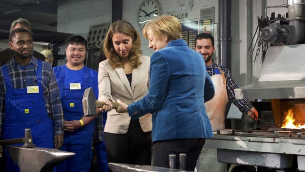 German Chancellor Merkel and German integration officer Oezog lift a smith hammer during their visit of trainees at the public transport company BVG in Berlin