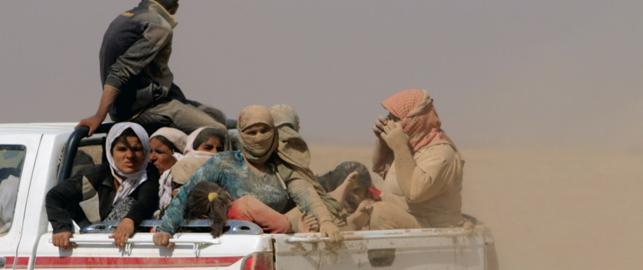 Displaced people from minority Yazidi sect, fleeing violence from forces loyal to Islamic State in Sinjar town, ride truck as they make way towards Syrian border, on outskirts of Sinjar mountain
