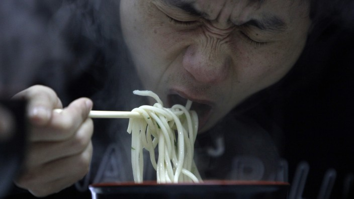 A man eats noodle at a restaurant in Shanghai