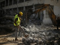 Palestinian worker carries a hammer as he participates in efforts to clear the rubble of a school in the east of Gaza City