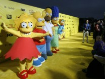 Characters Lisa, Bart, Homer, Marge and Maggie stand by a cake at the 20th anniversary party for the television series 'The Simpsons' in Santa Monica