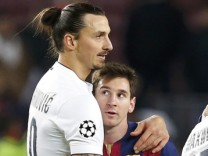 Paris St Germain's Zlatan Ibrahimovic embraces Barcelona's Lionel Messi after their Champions League Group F soccer match at the Nou Camp stadium in Barcelona