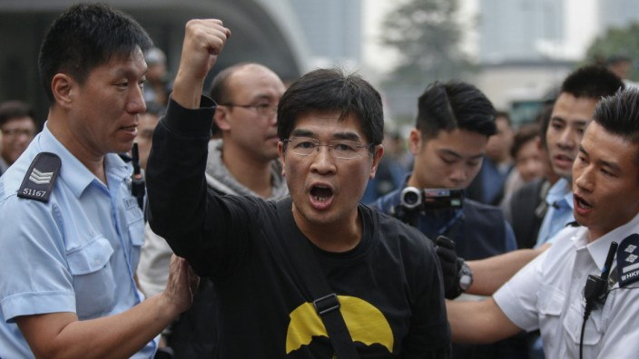 A demonstrator shouts slogan as he is taken away by police officers at an area previously blocked by pro-democracy supporters, outside the government headquarters in Hong Kong