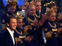 German TV show host Lanz smiles next to cheerleaders during the final German game show 'Wetten Dass..?' (Bet it...?) in Nuremberg
