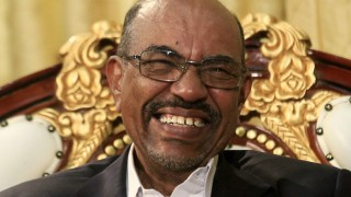 Sudan's President Omar al-Bashir laughs during an interview with the Russia Today news channel at the Presidential Palace in Khartoum