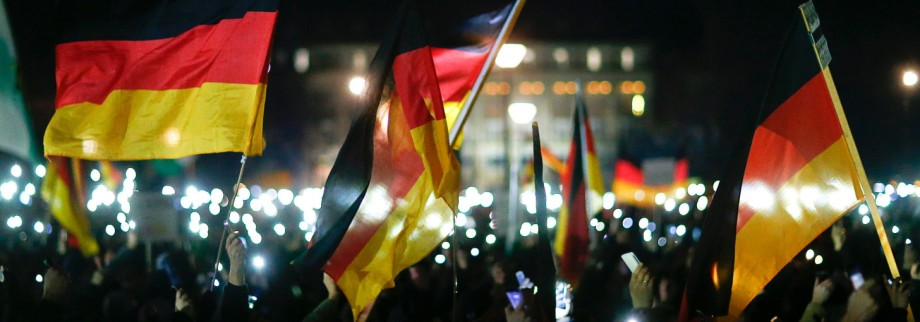 Participants hold up their mobile phones and wave German national flags during a demonstration called by anti-immigration group PEGIDA in Dresden