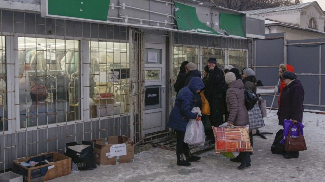 Refugees from eastern Ukraine queue to collect clothing donated to a volunteer centre in Kiev