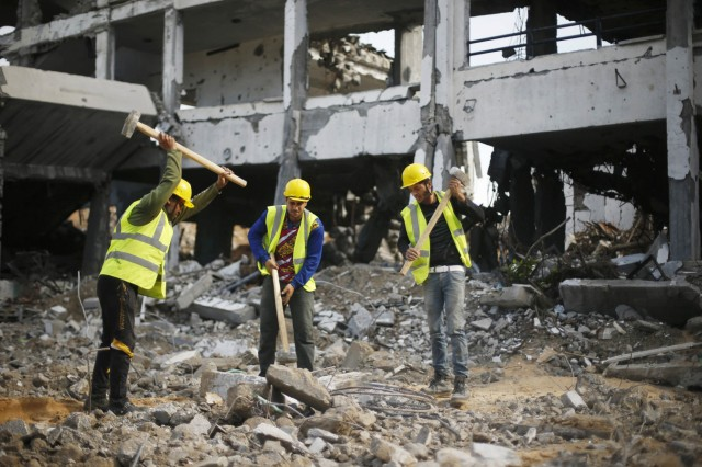 Palestinian workers participate in efforts to clear the rubble of a school that witnesses said was destroyed by Israeli shelling during the most recent conflict between Israel and Hamas, in the east of Gaza City
