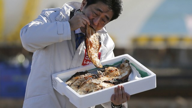 Japan PM Abe eats a local grilled fish during his official campaign kick-off for the Dec 14 lower house election, in Soma