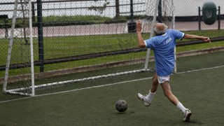 A senior soccer player runs to score a goal during a match at a soccer field in Miraflores