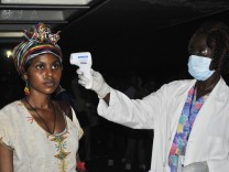 An Ethiopian health worker has her temperature taken upon arrival at Roberts airport outside Monrovia