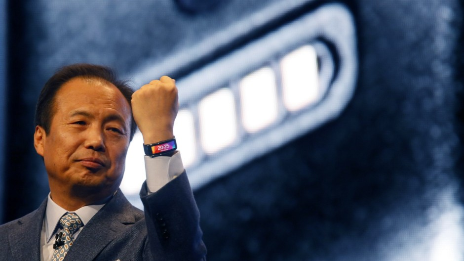 File photo of Shin, president and Head of IT and Mobile Communication Division of Samsung Electronics, showing off company's new Gear Fit fitness band during its launching ceremony at the Mobile World Congress in Barcelona