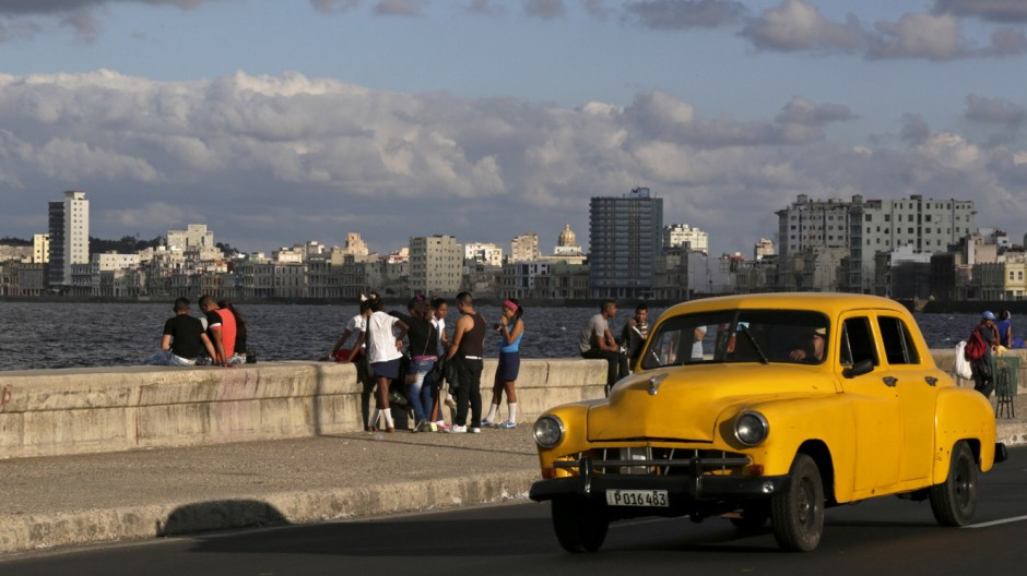 Youth sit on Havana's El Malecon seafront bolulevard