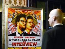 Mitarbeiter eines Sicherheitsdienstes vor einem Filmplakat von The Interview
