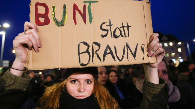Counter protester holds up a sign during a demonstration called by anti-immigration group PEGIDA, in Dresden