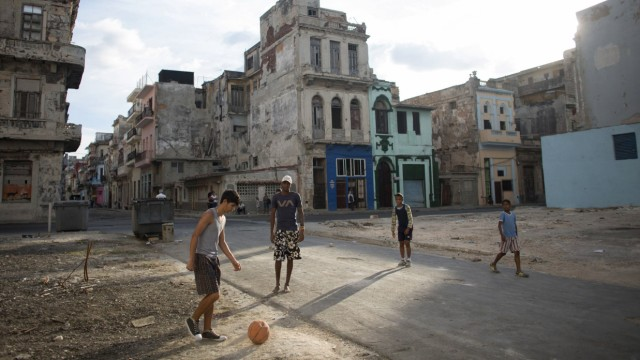 People play soccer on the street in downtown Havana