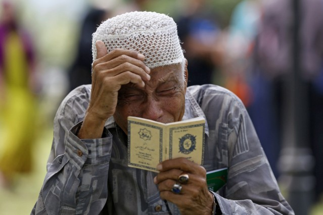 An Acehnese man cries while praying for a tsunami victim at a mass graveyard in Banda Aceh