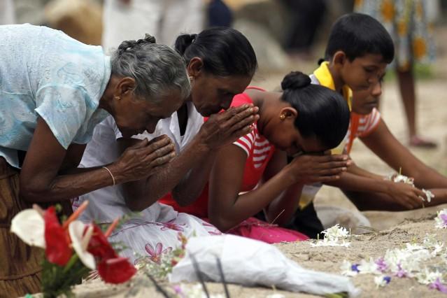Relatives of tsunami victims pray near a mass grave in Pereliya