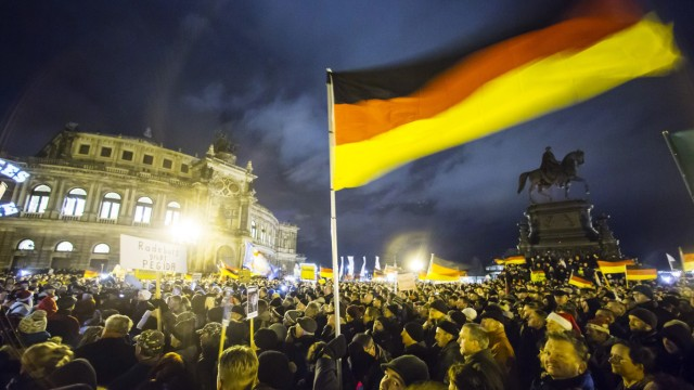 Participants hold German national flags during a demonstration organised by anti-immigration group PEGIDA in Dresden