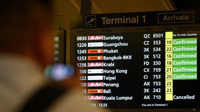 A flight information signboard shows the status of AirAsia flight QZ 8501 from the Indonesian city of Surabaya to Singapore at Changi Airport in Singapore