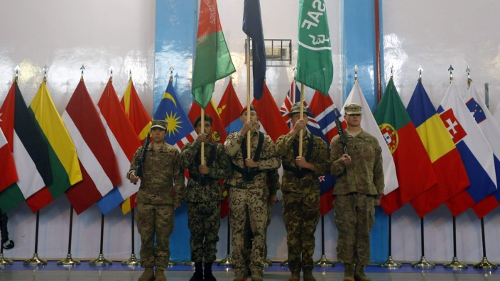 Afghan and NATO-led ISAF soldiers stand at attention during the change of mission ceremony in Kabul