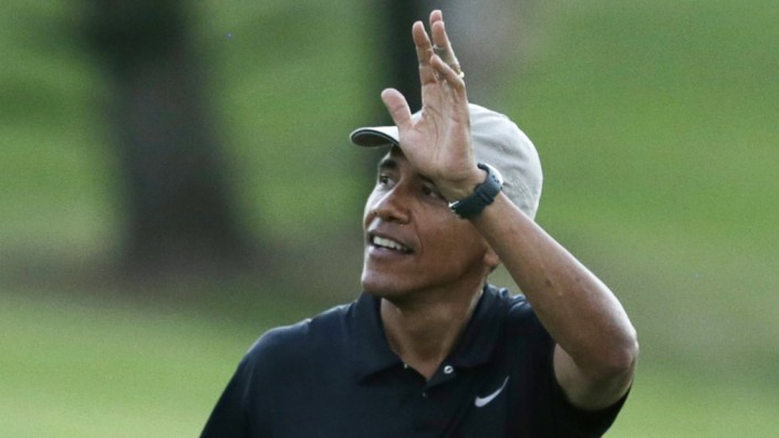 Obama waves to crowd at Mid-Pacific Country Club in Kailua during Hawaiian holiday vacation