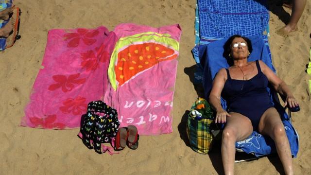 A woman sunbathes on San Lorenzo beach in Gijon