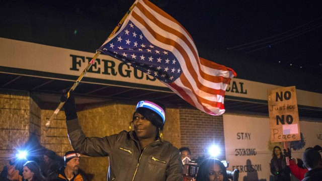Woman holds an upside-down American flag from a moving vehicle as she takes part in protest near the Ferguson Police Station in Ferguson