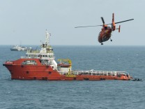 An Indonesian rescue helicopter flies over Crest Onyx ship as divers (R-in rubber boats) conduct operations to lift the tail of AirAsia flight QZ8501 in the Java Sea