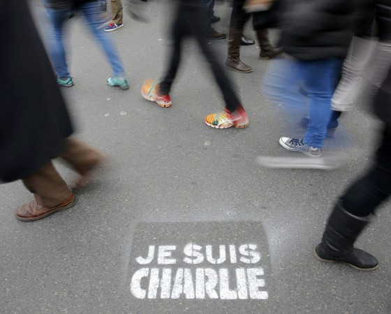 People walk past a grafitti tag reading 'I am Charlie' as they take part in a solidarity march (Marche Republicaine) in the streets of Paris