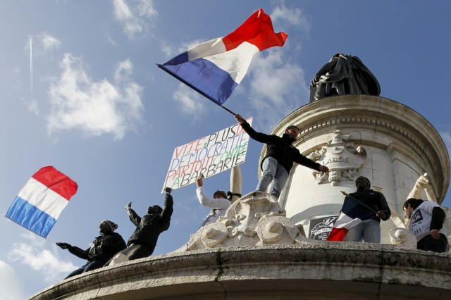 People holding a poster reading 'Quick more democracy everywhere against barbarism' take part in a solidarity march (Marche Republicaine) in the streets of Paris