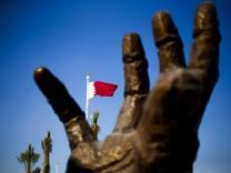Die Nationalflagge von Katar hinter einer Skulptur in Doha