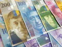 Swiss Franc and Euro banknotes of several values lie on a table in a Swiss bank in Bern