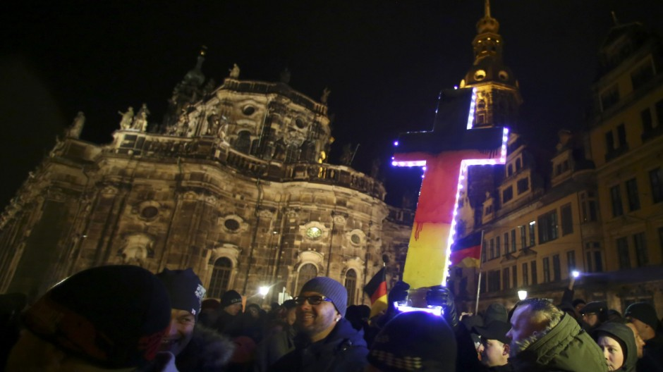 Participants hold a cross painted in the colours of German national flag during a demonstration called by anti-immigration group PEGIDA, a German abbreviation for 'Patriotic Europeans against the Islamization of the West', in Dresden