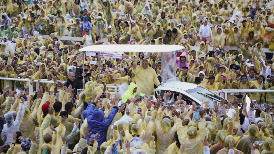 Pope Francis, wearing a yellow raincoat, waves to pilgrims after holding a mass at Tacloban's airport