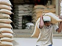 Tagelöhner trägt Reissack auf Landwirtschaftsmarkt