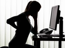 Silhouette of woman at desk having back pain model released Symbolfoto PUBLICATIONxINxGERxSUIxAUTxHU