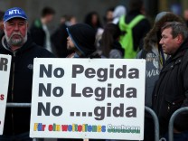 Anti-LEGIDA and PEGIDA protestors stand witha placard prior to LEGIDA demonstration in Leipzig