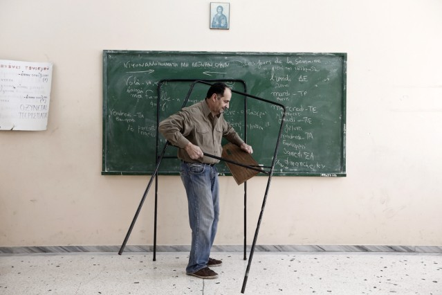 Man prepares a voting booth at an Athens high school that will used as a polling station