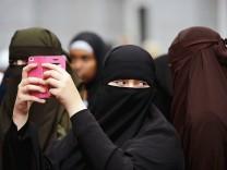 Ein verschleierte Muslima filmt die Rede von Salafistenprediger Pierre Vogel bei einer Kundgebung ra