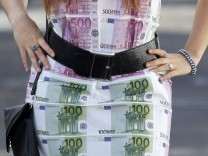 A woman wears a home-made dress featuring imitation 100 and 500 euro notes as she walks in Bordeaux