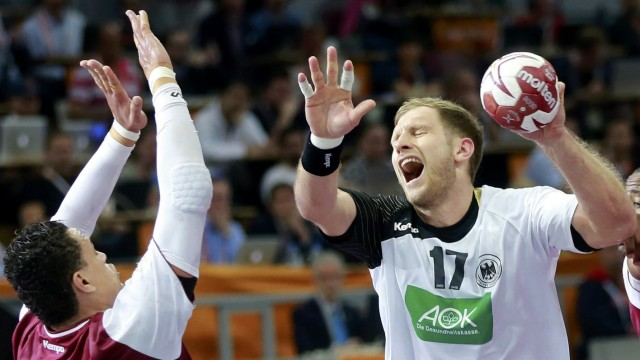 Weinhold of Germany is challenged by Benali of Qatar during their quarterfinal match of the 24th Men's Handball World Championship in Doha
