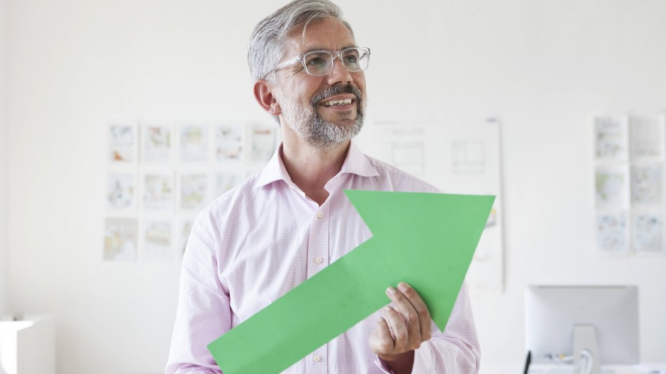 Portrait of smiling businessman holding green arrow model released Symbolfoto property released PUBL