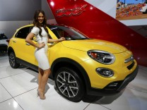 Model poses next to a 2016 Fiat 500X during the second press day of the North American International Auto Show in Detroit