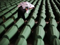A Bosnian Muslim cries near coffins prepared for a mass burial at the Memorial Center in Potocari, near Srebrenica