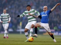 Celtic's Izaguirre is challenged by Rangers' Law during their Scottish League Cup semi final soccer match in Glasgow