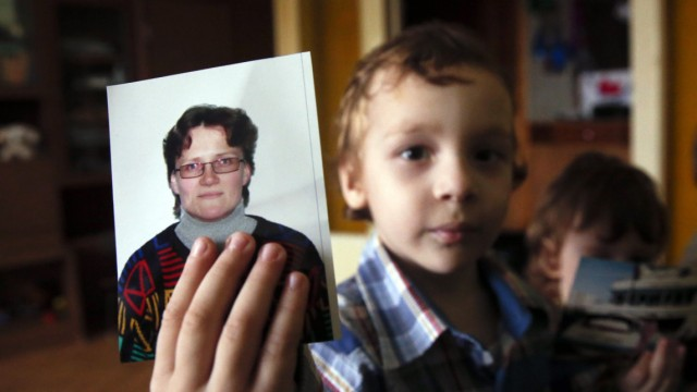 Artur, son of Russian activist Davydova and her husband Gorlov, holds up a photo of his mother to the camera, at their home in Vyazma