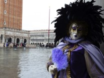 A masked reveller poses along the flooded St. Mark's Square during a period of seasonal high water and on the first day of carnival, in Venice
