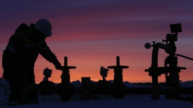 A worker checks the valve of an oil pipe at an oil field owned by Bashneft company near Nikolo-Berezovka