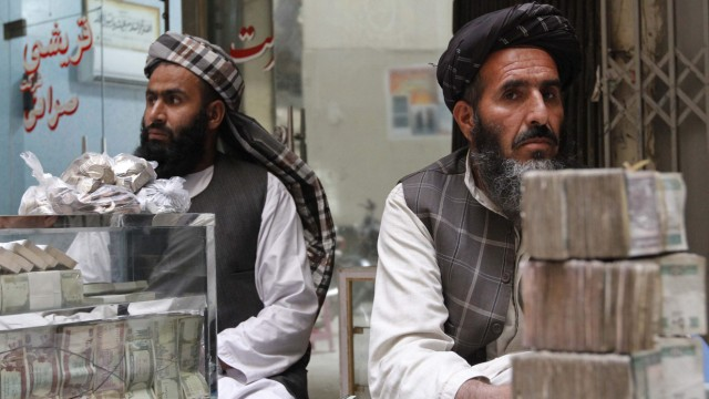 Afghan dealers wait for customers at a money market in Kandahar